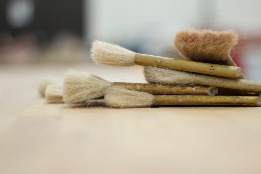 筆とヘラで木製サーフボードの仕上げ